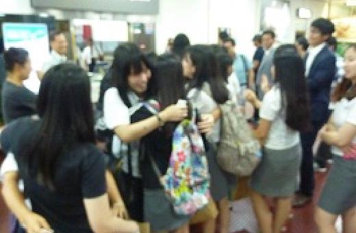 空港でハグして別れを惜しむ両校生徒